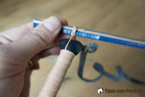 Stift mit darumgewickeltem Fadenende und Longierpeitsche mit Takelung