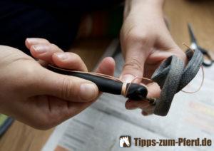 Der Anfang einer Wickelung, um die Lederschlaufe an der Peitsche zu befestigen